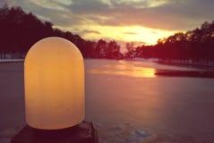 在一个冻湖的五颜六色的冬天日落有在前景的街灯的 免版税库存图片