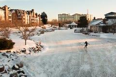 在一个冻湖的孤立花样滑冰运动员傍晚 免版税库存照片