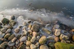 在一个冻湖的岩石 库存照片
