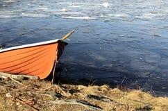 在一个冻湖的岸的橙色救助艇 免版税库存图片