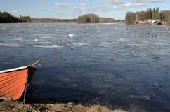 在一个冻湖的岸的橙色救助艇 库存图片