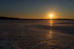 在一个冻湖的美好的日落 免版税图库摄影