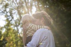 在一个年轻父亲和他的小孩儿子之间的嫩爱恋的片刻 免版税库存照片