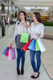 在一个购物中心的两逗人喜爱的女孩步行与礼物请求 免版税库存图片