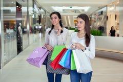 在一个购物中心的两逗人喜爱的女孩步行与礼物请求 库存图片