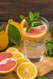 在一个玻璃烧杯的新鲜的柠檬水有冰的,绿色薄菏,红色orang 免版税库存照片
