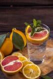 在一个玻璃烧杯的新鲜的柠檬水有冰的,绿色薄菏,红色orang 库存照片
