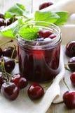 在一个玻璃瓶子和成熟莓果的樱桃果酱 库存照片