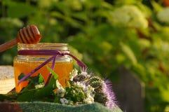 在一个玻璃瓶子和蜂蜂窝的蜂蜜用木表面上的花产蜜草本 免版税库存图片