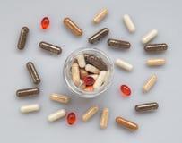 在一个玻璃瓶子外面的另外医药胶囊溢出在光 图库摄影