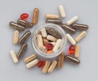 在一个玻璃瓶子外面的另外医药胶囊溢出在光 库存照片