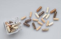 在一个玻璃瓶子外面的医药胶囊溢出轻的表面上 库存图片