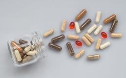 在一个玻璃瓶子外面的医药胶囊溢出轻的表面上 库存照片