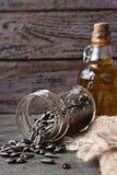 在一个玻璃瓶子的向日葵种子在木桌上 免版税库存图片