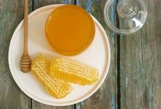 在一个玻璃瓶子的在蜂窝的蜂蜜和蜂蜜在老木背景 免版税库存图片
