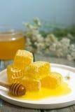 在一个玻璃瓶子的在蜂窝的蜂蜜和蜂蜜在老木背景 免版税库存照片