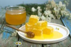 在一个玻璃瓶子的在蜂窝的蜂蜜和蜂蜜 免版税库存图片