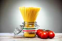 在一个玻璃瓶子的意大利意粉用蕃茄 免版税库存图片