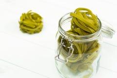 在一个玻璃瓶子的未加工的绿色tagliatelle面团 免版税库存照片