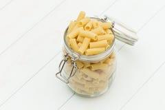 在一个玻璃瓶子的未加工的tortiglioni面团 免版税库存照片