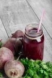 在一个玻璃瓶子的甜菜汁在木背景 切甜菜根和新鲜的荷兰芹 菜震动 复制空间 免版税库存图片