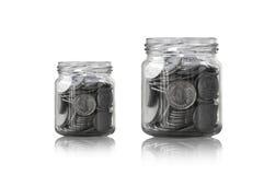 在一个玻璃瓶子的硬币反对,储款铸造-投资和兴趣概念挽救金钱概念 免版税库存照片