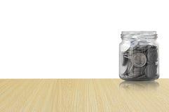 在一个玻璃瓶子的硬币在木地板上,储款铸造-投资和兴趣概念挽救金钱概念 免版税库存图片
