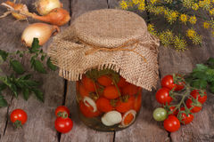 在一个玻璃瓶子的罐装西红柿在木 免版税库存照片
