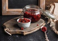在一个玻璃瓶子的自创山莓果酱在一个木板的一个小碗在桌上 库存照片