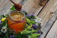 在一个玻璃瓶子的蜂蜜用木表面上的花产蜜草本 免版税库存图片