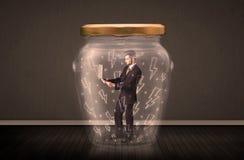 在一个玻璃瓶子里面的商人有闪电图画概念的 图库摄影