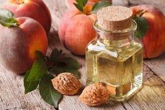 在一个玻璃瓶的化妆油桃子在桌特写镜头 展望期 免版税库存图片