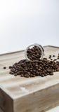 在一个玻璃瓶的咖啡豆在木背景 免版税库存图片