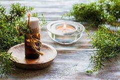 在一个玻璃瓶的杜松精油在一张木桌上 使用在医学、化妆用品和芳香疗法 图库摄影