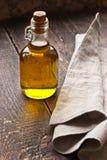在一个玻璃瓶的橄榄油在土气桌上 免版税库存图片