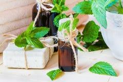 在一个玻璃瓶的薄荷精油在一张轻的桌上 使用在医学、化妆用品和芳香疗法 免版税库存图片