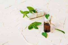 在一个玻璃瓶的薄荷精油在一张轻的桌上 使用在医学、化妆用品和芳香疗法 图库摄影