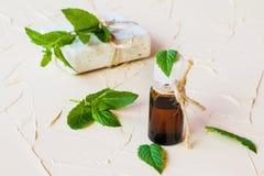 在一个玻璃瓶的薄荷精油在一张轻的桌上 使用在医学、化妆用品和芳香疗法 免版税图库摄影