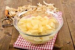 在一个玻璃碗的切成小方块的土豆用水 免版税库存照片