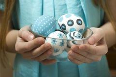 在一个玻璃碗的复活节彩蛋由女孩对负手中 免版税库存照片