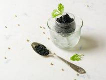 在一个玻璃碗的黑鱼子酱有冰的 生来有福和白色背景 库存照片