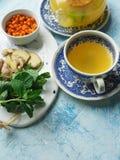 在一个玻璃罐的新近地酿造的茶海鼠李莓果、薄菏和姜 免版税图库摄影