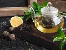 在一个玻璃罐的新近地酿造的绿茶用柠檬和薄菏 免版税库存照片