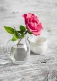在一个玻璃花瓶的桃红色玫瑰白色表面上 库存照片