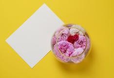 在一个玻璃花瓶的玫瑰,在黄色背景 平的位置静物画概念 免版税库存图片