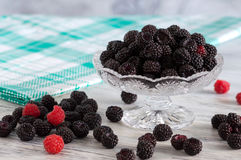在一个玻璃花瓶的黑树莓在一张白色木桌上 在鸠笼子的餐巾 免版税图库摄影