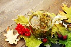 在一个玻璃透明杯子的清凉茶在秋叶用一朵红色guelder玫瑰和dogrose的莓果 免版税库存图片
