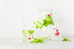 在一个玻璃水罐和玻璃的戒毒所水 莓果和石灰、红色和绿色 新鲜的叶子薄菏 免版税库存图片