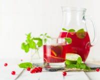 在一个玻璃水罐和玻璃的蜜饯 莓果和石灰、红色和绿色 新鲜的叶子薄菏 复制空间 库存图片