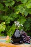 在一个玻璃水罐的黑老香醋用新鲜的红葡萄 免版税库存照片